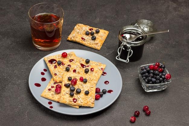 Ciastka z jagodami na szarym talerzu. słoik dżemu, szklanka herbaty i jagody w misce. czarne tło. widok z góry
