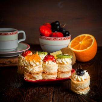 Ciastka z kremem i owocami z filiżanką herbaty i półmisek owoców i pomarańczą w talerzu