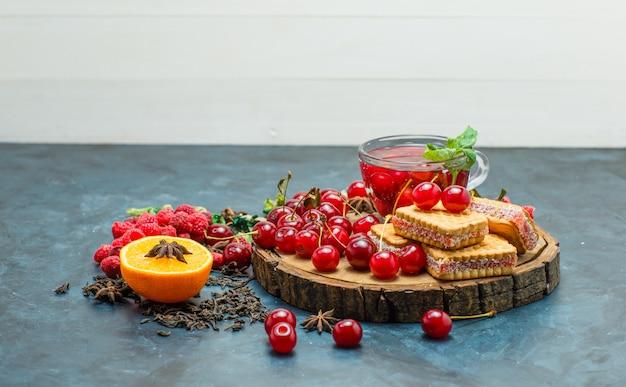 Ciastka z ziołami, owocami, herbatą, przyprawami, deska na tle białym i sztukaterie, widok z boku.