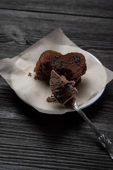 Ciastko czekoladowe deserowe w formie serca leży na drewnianym tle