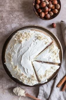 Ciastko domowej roboty z orzechami i przyprawami udekorowane kremem maślanym lub polewą serową