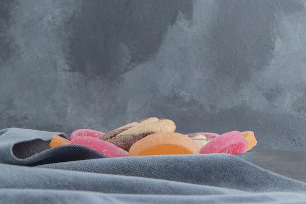 Ciastko i marmolady na obrusie na marmurze.