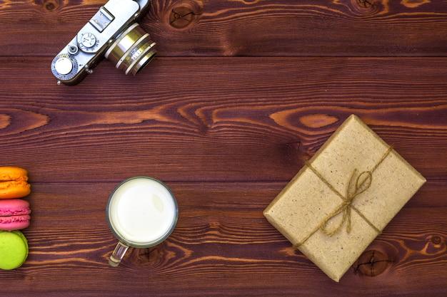 Ciastko macaroon i prezent zawijający w papierze w retro stylu na stole