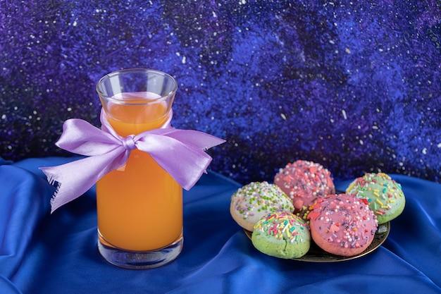 Ciastko ozdobione cukierkami i szklanką soku.