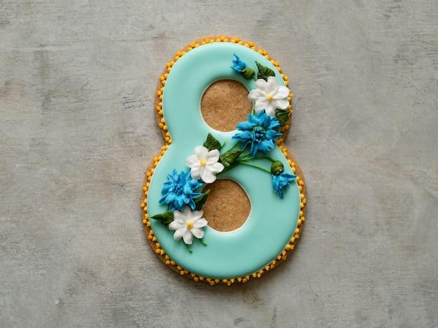 Ciastko pokryte niebieską glazurą wykonane w formie ósemki z kwiatami - chabry i stokrotki - na szarym tle