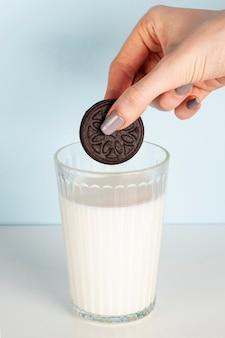 Ciastko trzymający nad szkło mleka widoku długi strzał
