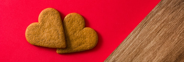 Ciastko w kształcie serca na czerwonym tle. widok panoramiczny. koncepcja walentynki i dzień matki.
