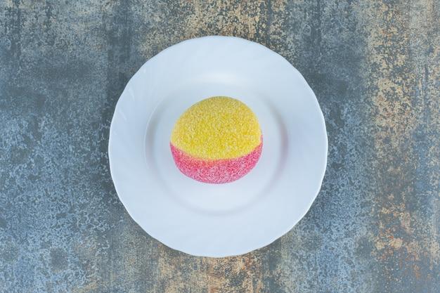 Ciastko w postaci brzoskwiń na talerzu, na marmurowej powierzchni.
