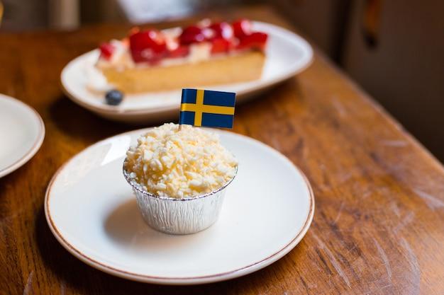 Ciastko z flagą szwecji. zestaw różnych ciast. bliska ciasto truskawkowe