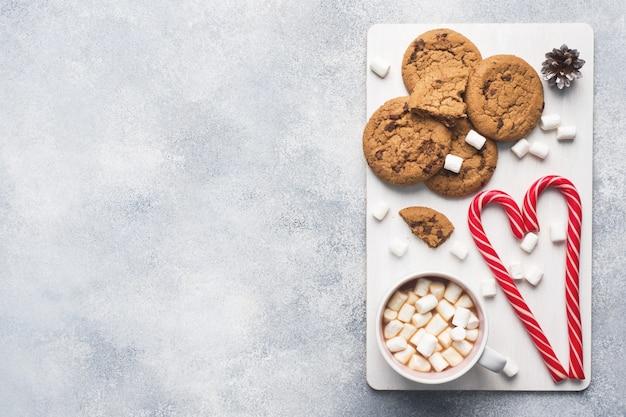 Ciastko z kawałkami czekolady, świąteczny karmel z trzciny cukrowej cup kakao i rożki zefir ozdoby na szaro. copyspace frame.