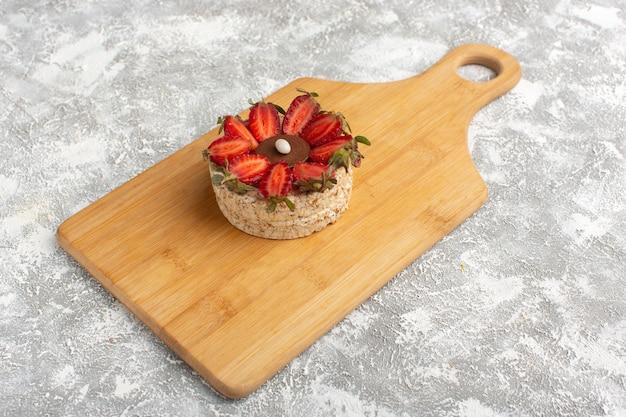 Ciastko z truskawkami na drewnianym biurku