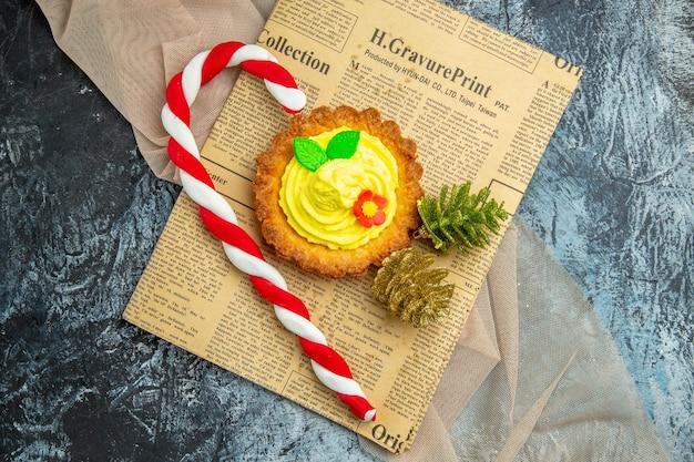 Ciastko z widokiem z góry z ozdobami świątecznymi na gazecie na ciemnym tle