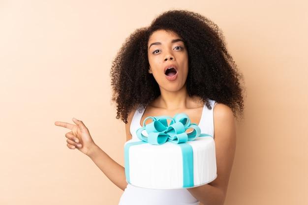 Ciasto afro kucharz trzyma duży tort na białym tle