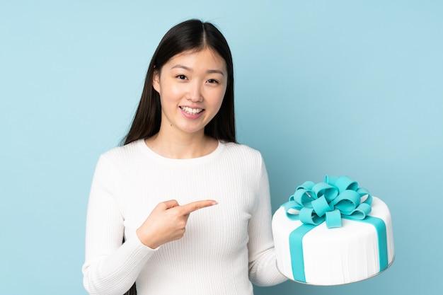 Ciasto azjatykci szef kuchni trzyma dużego tort na błękit ścianie i wskazuje je