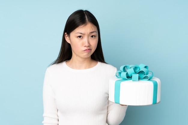 Ciasto azjatykci szef kuchni trzyma dużego tort odizolowywający na błękit ścianie z smutnym wyrażeniem