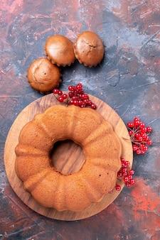Ciasto babeczki smaczne ciasto z czerwonymi porzeczkami na desce i trzema babeczkami