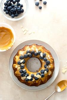 Ciasto bananowe bundt z polewą z masła orzechowego. zdrowe bezglutenowe ciasto z nasionami chia ozdobione jagodami i płatkami migdałów.