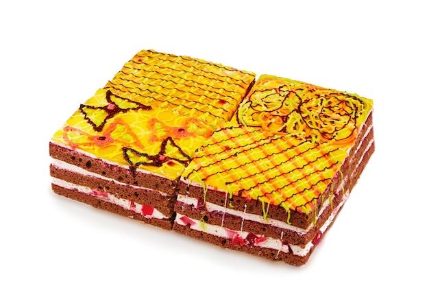 Ciasto biszkoptowe czekoladowe zdobione ornamentem glazury na białym tle