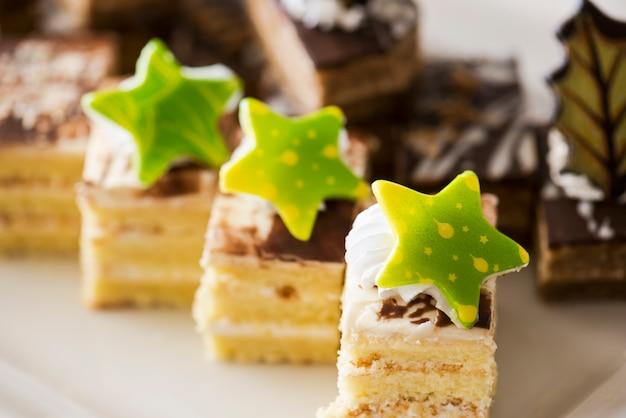 Ciasto biszkoptowe, ozdobione kremem i białą czekoladą na białym talerzu. selektywne ustawianie ostrości