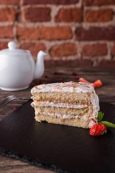 Ciasto biszkoptowe ze śmietaną i karmelem na kamiennym talerzu na rustykalnym stole z drewna