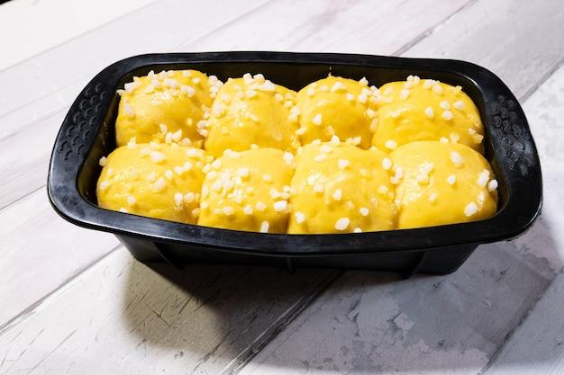 Ciasto brioche z masłem i cukrem w silikonowej formie przed włożeniem do piekarnika