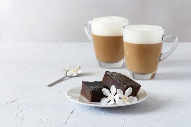 Ciasto brownie ozdobione kwiatami i dwiema filiżankami kawy.