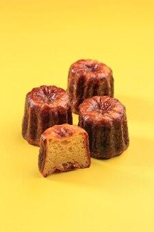 Ciasto canele bordeaux, francuski słodki deser. skopiuj miejsce na tekst na żółtym tle. jedna z odciętych połówek, wybrane skupienie