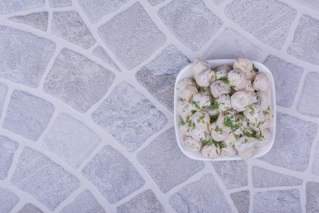 Ciasto chinkali z farszami i posiekanymi ziołami w białej misce.