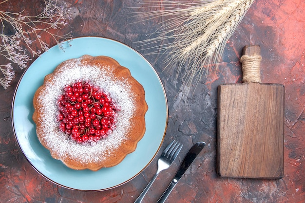 Ciasto ciasto z czerwonymi porzeczkami drewniana deska do krojenia nóż i widelec