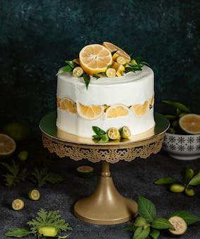 Ciasto cytrynowe ozdobione białą śmietaną i owocami cytrusowymi