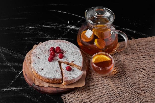 Ciasto cytrynowe z jagodami na drewnianym talerzu.