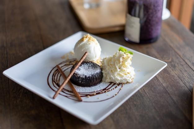 Ciasto czekoladowe i lody waniliowe są pięknie umieszczone na talerzu.