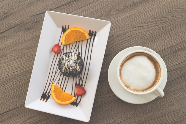 Ciasto czekoladowe lub ciasto czekoladowe z lawy ze świeżymi owocami i kawą na drewnianym tle