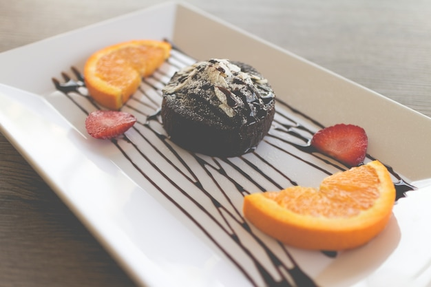 Ciasto czekoladowe lub czekoladowe ciasto lawowe ze świeżymi owocami i kawą