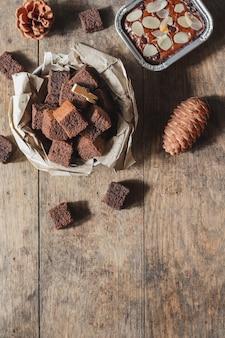 Ciasto czekoladowe mini brownie, deser z mlekiem na ciemnym tle na drewnianym stole.