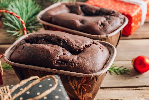 Ciasto czekoladowe na prezent na drewnianej desce do krojenia z dekoracjami świątecznymi na rustykalnym tle. selektywna ostrość