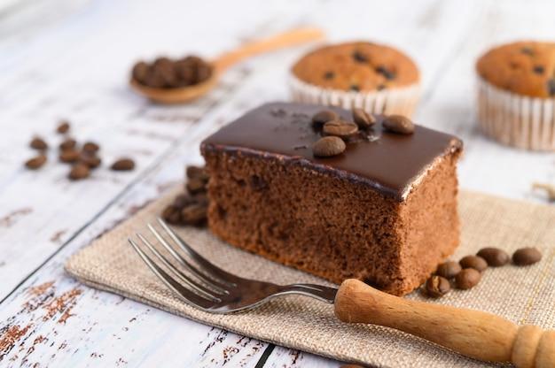 Ciasto czekoladowe na worku i ziarna kawy z widelcem na drewnianym stole.