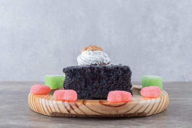 Ciasto czekoladowe otoczone galaretką na półmisku na marmurowej powierzchni