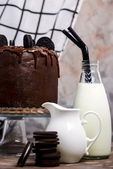 Ciasto czekoladowe ozdobione ciasteczka na szklanej podstawce wśród naczyń