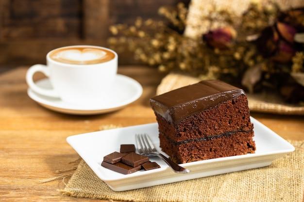 Ciasto czekoladowe ozdobione kawałkiem czekolady i widelcem na białym talerzu z filiżanką kawy latte