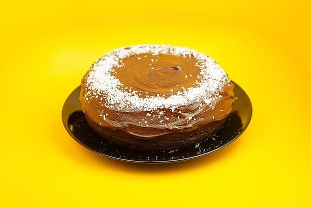 Ciasto czekoladowe ozdobione płatkami kokosowymi, domowe ciasto na żółtej powierzchni. całe domowe ciasto z dodatkiem kakao na czarnym talerzu ceramicznym