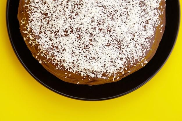 Ciasto czekoladowe ozdobione płatkami kokosowymi, domowe ciasto na żółtym tle, widok z góry. połowa domowego ciasta ze składnikiem kakao na czarnym talerzu ceramicznym