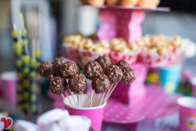 Ciasto czekoladowe wyskakuje na świątecznym stole deserowym na przyjęciu urodzinowym dla dzieci