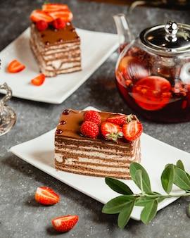 Ciasto czekoladowe z białą śmietaną skropione kakao i jagodami