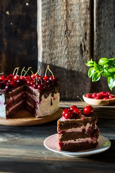 Ciasto czekoladowe z bitą śmietaną. ciasto wiśniowe z czekoladą. malinka w drewnianym talerzu.