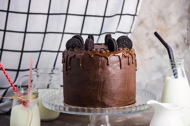 Ciasto czekoladowe z herbatnikami na szklanym stojaku wśród naczyń