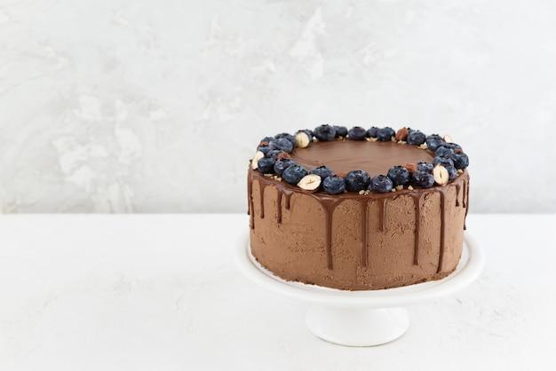 Ciasto czekoladowe z jagodami i orzechami na jasnym tle