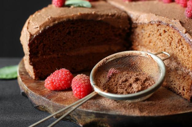 Ciasto czekoladowe z malinami. ciasto na ciemnym tle. sito z kakao w proszku