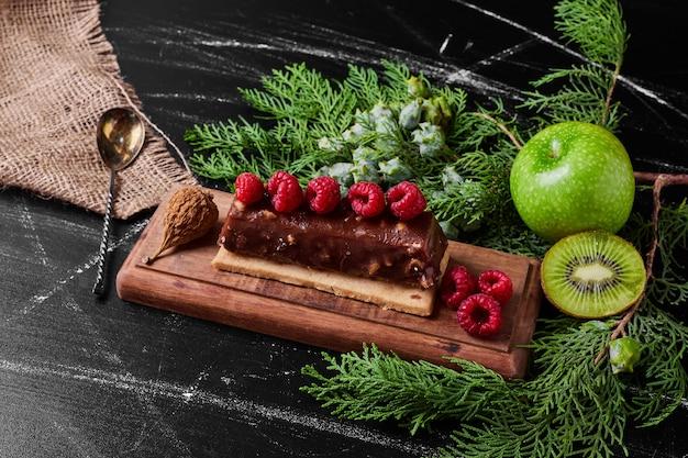 Ciasto czekoladowe z malinami na drewnianym talerzu.