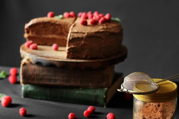 Ciasto czekoladowe z malinami na książkach. ciasto na ciemnym tle. sito i kakao